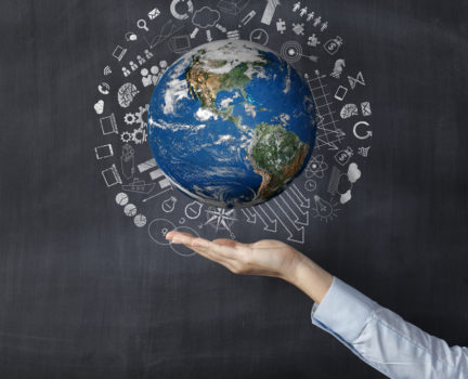 Businesswoman holding earth front of blackboard
