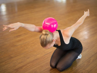 A rhythmic gymnast balancing the ball on her shoulder blades, with arms stretched in both directions