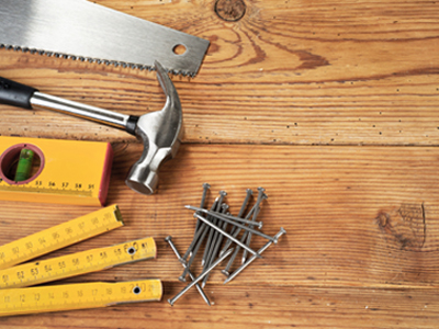 Handsaw, hammer, level, nails and folding ruler on wooden background
