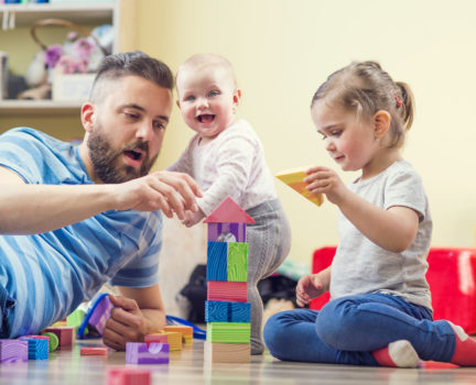 Young hipster father playing with his daughters