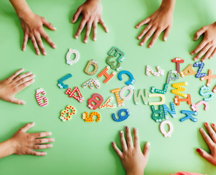 Top view of child hands with wooden toy plate alphabet