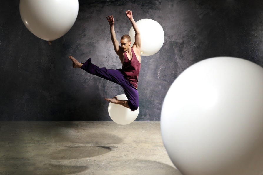 Young energetic dancer performs modern dance pose