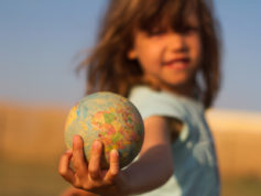 Front view of a child hand holding a damaged toy globe, shallow depth of field