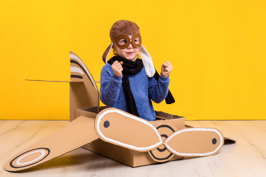 Little dreamer girl playing with a cardboard airplane. Childhood. Fantasy, imagination. Studio photography on a yellow background. Imagination or exploration concept